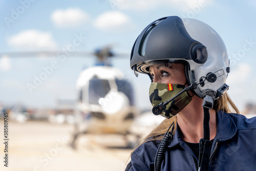 Female police pilot looking away while wearing protective face mask Poster Mural XXL