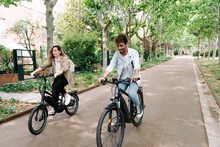 Couple Riding Electric Bicycles On Road