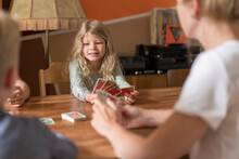 Cute Blond Girl Playing Cards With Family At Dining Table