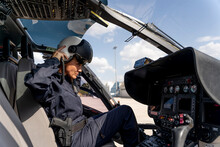 Female Police Pilot Wearing Helmet While Sitting At Cockpit In Helicopter