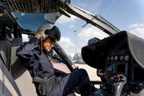 фотографія Female police pilot wearing helmet while sitting at cockpit in helicopter