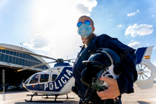 Photographie Female police pilot in face mask standing against sky on sunny day