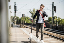 Smiling Man Talking On Mobile Phone While Walking With Push Scooter On Railroad Station Platform