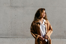 Young Woman Wearing Brown Coat Standing Against Wall
