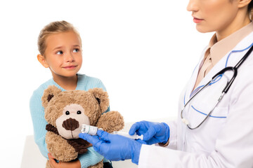 Selective focus of smiling girl with teddy bear sitting near doctor with syringe and vaccine isolated on white