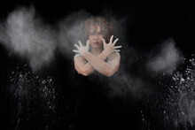 Woman Throwing White Dust Besides Herself While Standing Against Black Background
