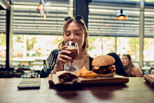 Woman Having A Beer And A Burg...