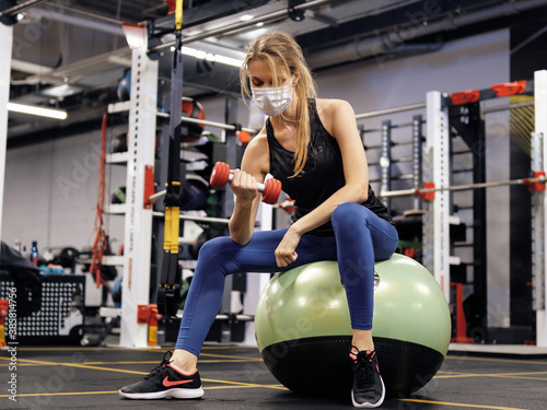 Obraz Pandemic gym - woman working out with protective face mask during coronavirus outbreak - fototapety do salonu