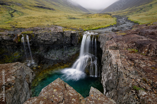 Scenic view of Skutafoss waterfall falling from cliff - 385814951