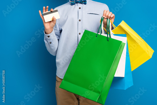 cropped view of boy holding shopping bags and credit card on blue Fotobehang