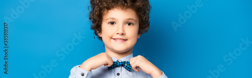 Obraz horizontal crop of curly kid in shirt touching bow tie and smiling on blue - fototapety do salonu