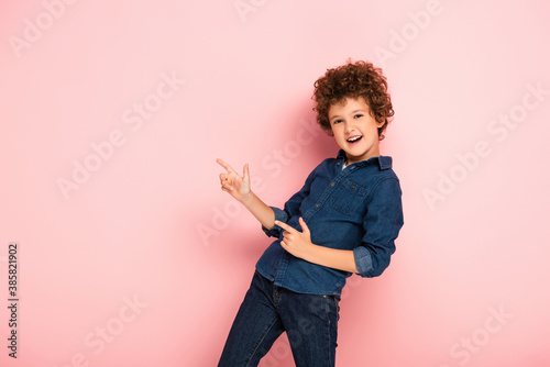 excited curly boy in denim shirt pointing with fingers on pink Wallpaper Mural