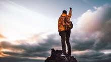 Hiker Standing On The Cliff Mountain Pointing The Sky With Fingers At Sunset. Successful Man On The Top Of The Mountains.