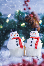 Two Iced Christmas Snowman Cupcakes With Carrot Nose, Santa Hat, And Scarf. Selective Focus With Blurred Foreground And Background.