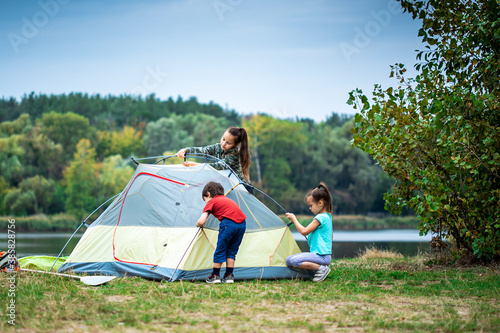 Obraz Children pitching a tent on the campsite near lake - fototapety do salonu
