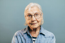 Wise Concentrated Old Woman With Attentive Gray Eyes In Big Round Glasses Looks Into Camera. Intelligent Elderly Lady Wearing Striped Shirt And Denim Jacket Isolated Over Gradient Blue Background.