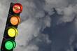 canvas print picture - Semaforo con luce rossa, arancione, gialla e verde accese e la scritta corona virus sulla luce rossa e il cielo tempestoso come sfondo