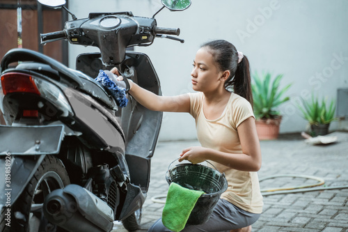 asian young girl washing his motorcycle scooter with soap and sponge at home