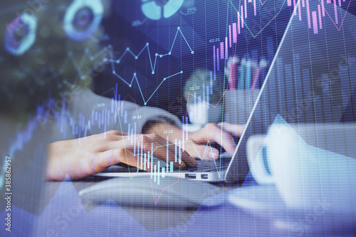 Double exposure of woman hands typing on computer and forex chart hologram drawing. Stock market invest concept.