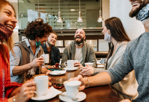Group of happy friends with face mask drinking espresso at coffee house  - Young Canvas