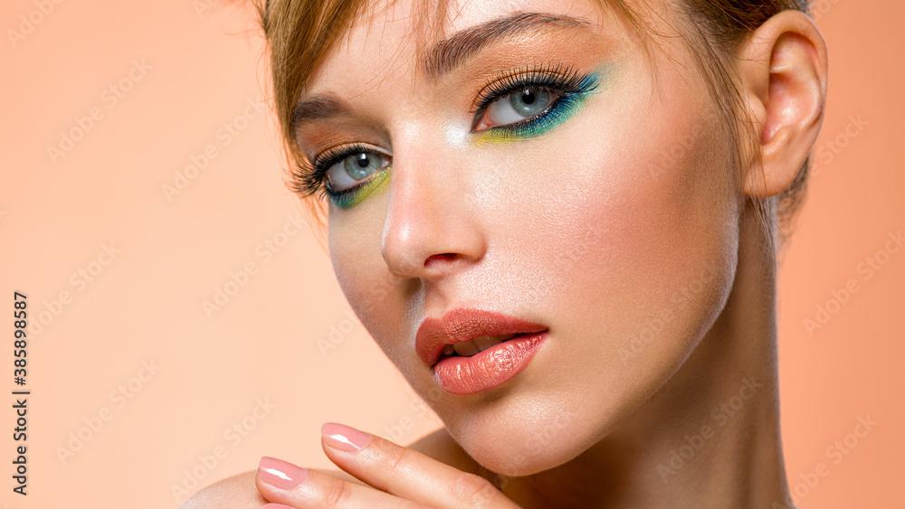 Fototapeta Face of an young girl close-up with a green color makeup. Stylish makeup.