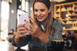 Leinwandbild Motiv Female texting on her mobile phone at cafe