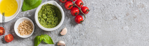 Fotografie, Obraz top view of raw tomatoes, garlic, basil, pine nuts, olive oil, pesto sauce on grey surface, panoramic shot