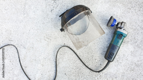 Canvas Print Plastic protective face shield and manual angle grinder equipped with a metal Stripping tool on gray concrete background