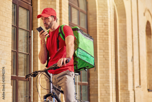 Fototapeta Young caucasian male courier talking on phone obraz