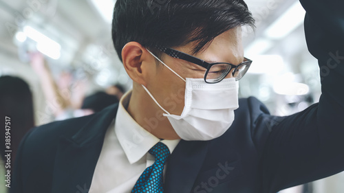 Obraz Young man wearing face mask travels on crowded subway train . Coronavirus disease or COVID 19 pandemic outbreak and urban lifestyle problem in rush hour concept . - fototapety do salonu