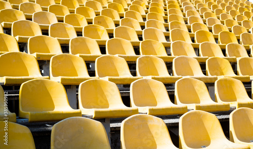 Fototapeta yellow tribunes. seats of tribune on sport stadium. empty outdoor arena. concept of fans. chairs for audience. cultural environment concept. color and symmetry. empty seats. modern stadium obraz