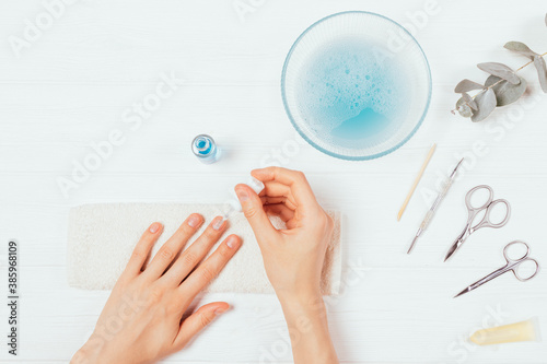 Female hands apply nail polish near set of tools Fototapet