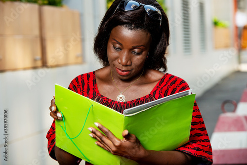 Fotografía adult african woman in red loincloth sitting with a document in hand