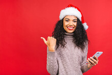 Happy Excited African American Woman In Red Santa Claus Hat With Mobile Phone Isolated Over Red Background. Pointing Finger.
