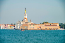 Panoramic Scenic View Of Venice Venezia Skyline With Bell Towers, Old Historic Buildings Palazzi Houses, Basilica Churches And San Marco Tower And Doge Palace And Maritime Traffic On Giudecca Canale
