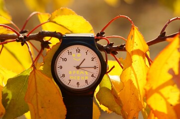 Hand-held clock on the background of autumn leaves. The inscription on the clock in Russian time of autumn.
