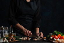 The Chef In Black Uniform Cuts With Knife Mushrooms On Chopped Board At The Professional Kitchen On Dark Background. Backstage Of Cooking Dinner With Meat, Vegetables And Spices. Food Concept.