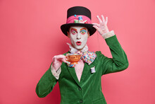 Photo Of Shocked Male Has Image Of Mysterious Hatter From Wonderland Wears Bright Makeup Poses With Cup Of Tea Dressed In Aristocratic Clothes Isolated On Pink Background. Halloween Party Concept