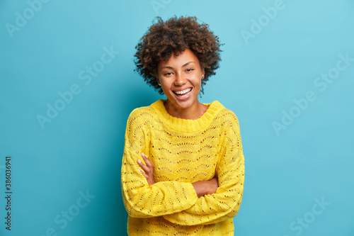 Obraz Happy joyful dark skinned woman laughs happily keeps arms folded and expresses positive emotions grins from happiness dressed in casual jumper isolated on blue background has fun or hears funny joke - fototapety do salonu