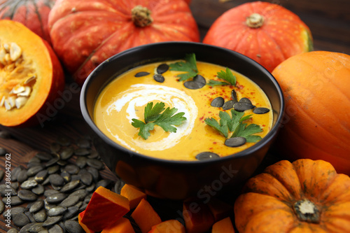 Roasted pumpkin and carrot soup with cream and pumpkin seeds on wooden background Fototapete