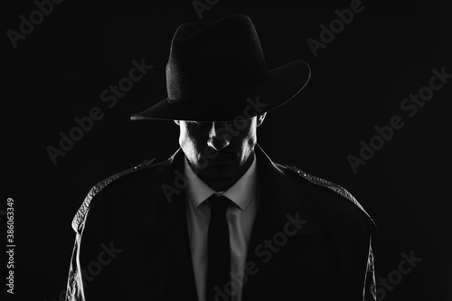 Old fashioned detective in hat on dark background, black and white effect Fototapeta