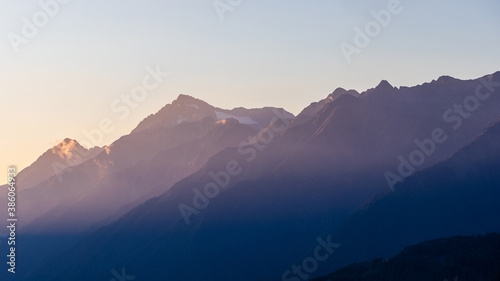 Obraz Sunset in the mountains, the rays of the setting sun on the peaks - fototapety do salonu