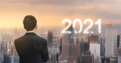 Fototapeta Businessman with futuristic 2021 city in sunrise. New business trend and investment in 2021 new year