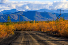 The Nature Of The Magadan Region. Forest Road Among Taiga During Golden Autumn. Dirt Road