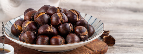 Fototapeta Close up of delicious roasted chestnuts with oil for eating.