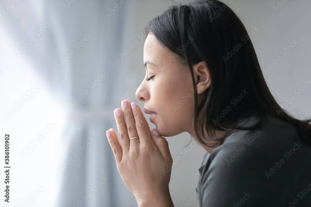 Fototapeta Close up of religious young African American woman hold hands in prayer ask beg to God. Superstitious biracial female believer pray feel grateful thankful. Religion, faith, superstition concept.