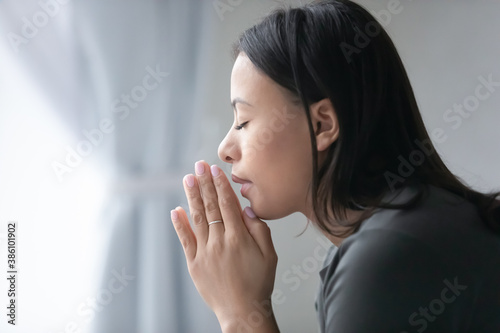 Photo Close up of religious young African American woman hold hands in prayer ask beg to God