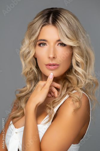 Obraz Studio portrait of young and beautiful woman over grey background. - fototapety do salonu