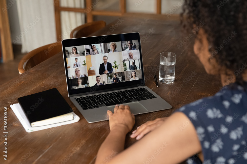 Fototapeta Rear view of female employee talk online video call with diverse multiracial colleagues at home office. Woman worker have webcam digital virtual conference or web meeting with businesspeople.