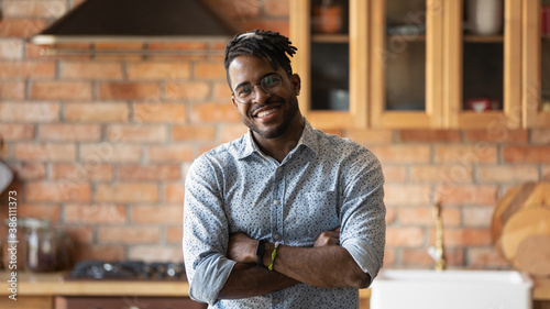 Fotomural Portrait of smiling millennial African American man in glasses pose in modern renovated home kitchen